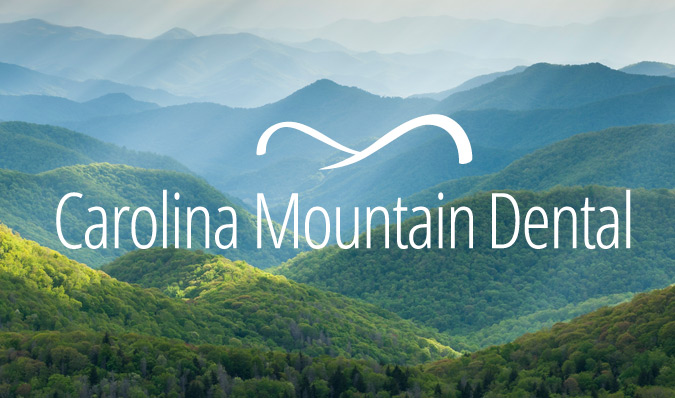 Carolina Mountain Dental logo overtop blue ridge mountains